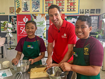 Heart Foundation Food and Nutrition Manager, Dave Monro with two students in classroom cooking