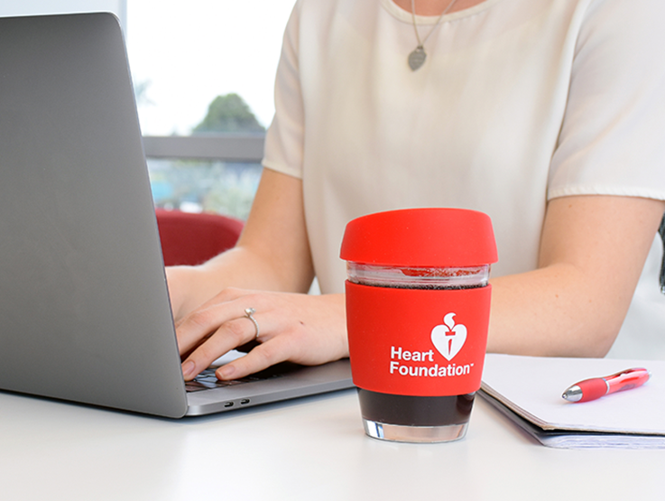 Heart Foundation branded coffee cup on desk