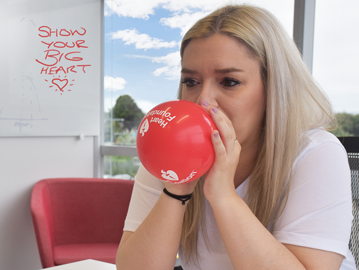 Woman blowing up balloons for fundraising event