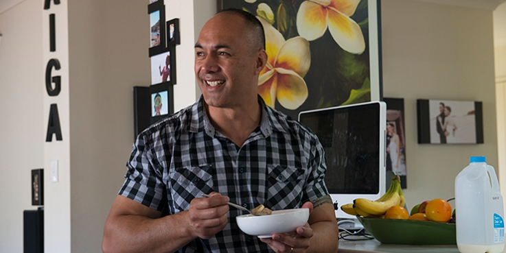 Man eating bowl of cereal in house