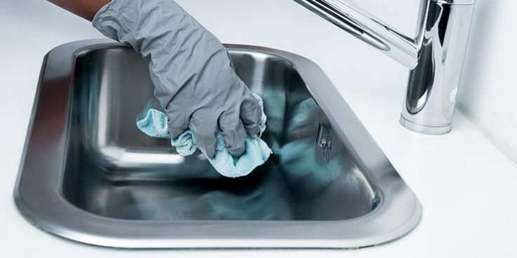 Person cleaning sink with rubber gloves on