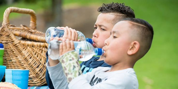 Child outside drinking bottled water