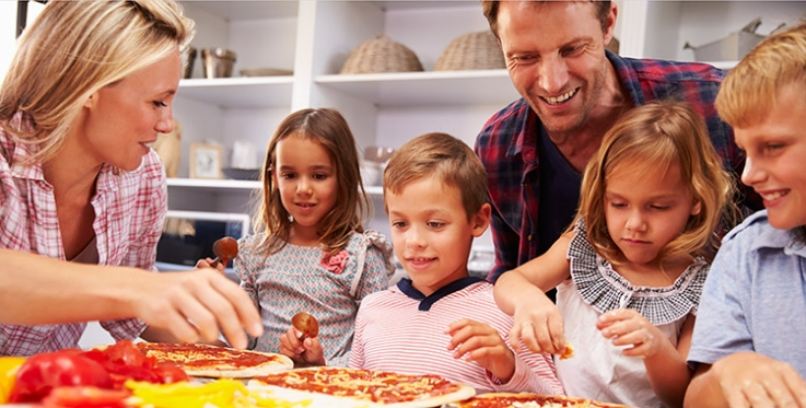 Mum, Dad and four kids, two sons and two daughters, in kitchen making pizza from scratch