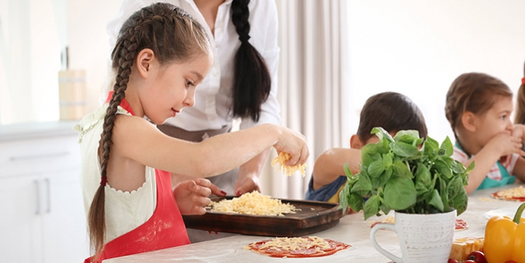 Young girl making pizza in kitchen