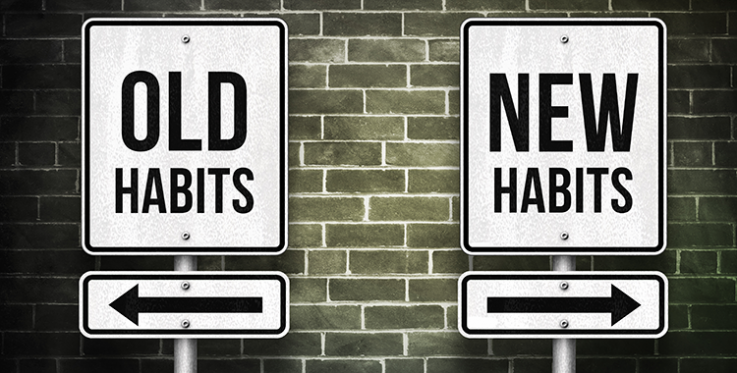 Two signs saying old habits and new habits pointing in different directions.