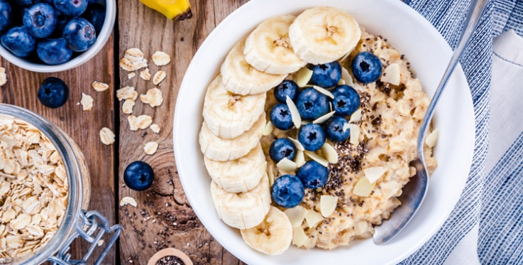 Whole grain porridge in a bowl with banana and blueberries