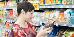 Woman reading food labels in supermarket