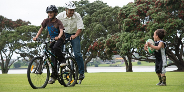 Dad on bike in park with two children, one child on a bike and one holding a rugby ball