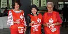 Volunteers holding buckets and wearing heart foundation bibs