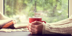 Woman holding warm drink on a rainy day