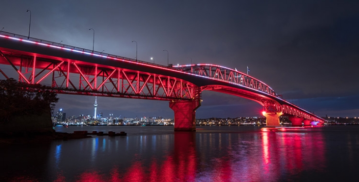 Auckland's Harbour Bridge lit up in red lights