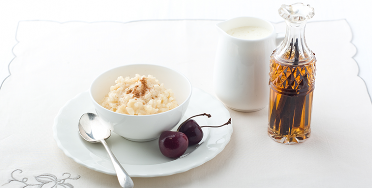 creamy rice pudding topped with brown sugar and served with a side of cherries