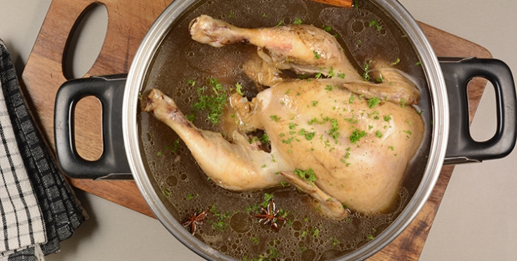 Seasoned chicken in pan of stock