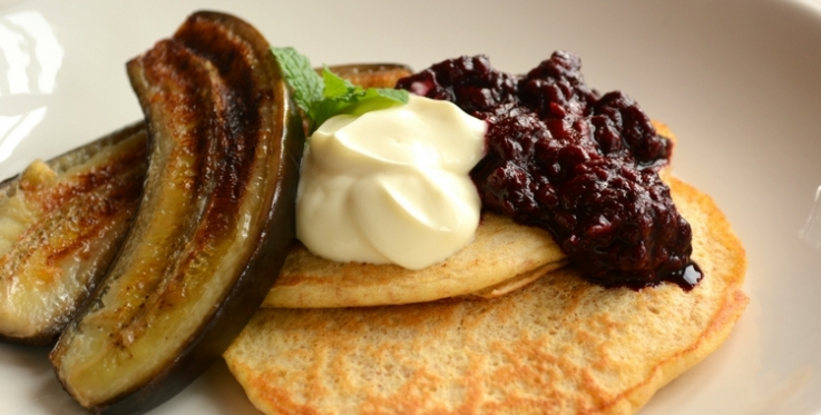 pancakes served with berry compote fried bananas and plain yoghurt