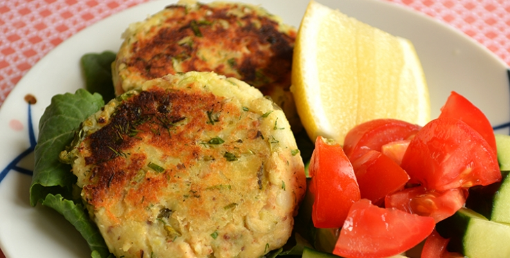 salmon and potato cakes served with lemon tomatoes and cucumber