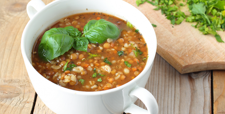 spicy red lentil soup in a bowl with basil garnish