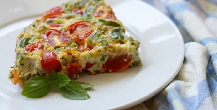 vegetable frittata with tomatoes green capsicum and cheese garnished with basil