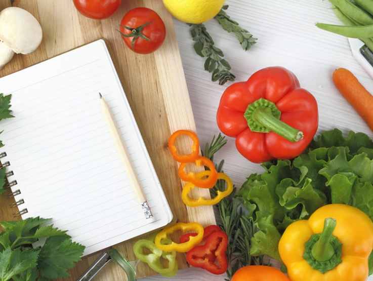 Blank note book surrounded by vegetables on a table